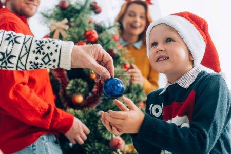 foyer sélectif de grand-père donnant boule de Noël au petit-fils étonné