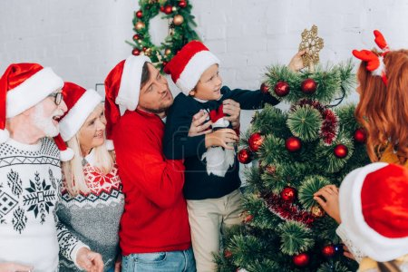 Photo for Father holding son in hands while decorating christmas tree together with family - Royalty Free Image