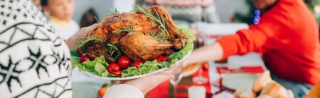Photo for Panoramic crop of senior man holding plate with delicious roasted turkey, cherry tomatoes and lettuce - Royalty Free Image