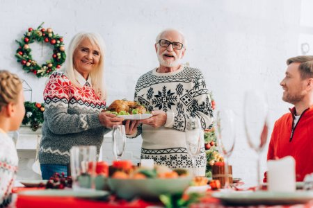 Selective focus of elderly people with turkey near family and festive table
