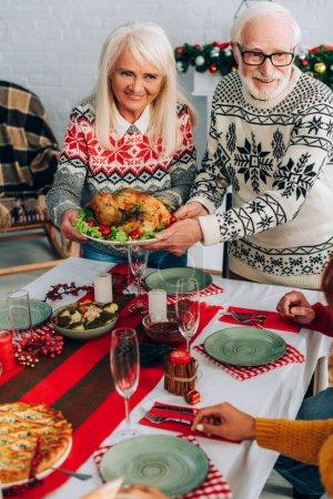 Photo pour Grand-parents souriants servant la dinde sur la table de fête près de la famille à la maison - image libre de droit