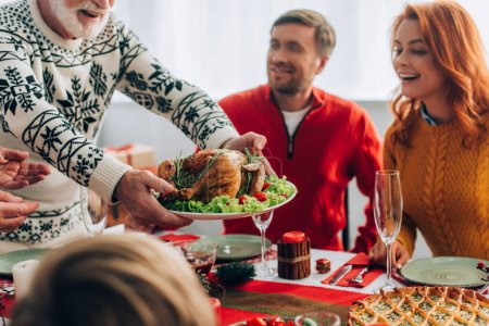 Photo for Selective focus of granddad serving turkey on festive table near family at home - Royalty Free Image