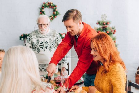 Smiling man cutting turkey on festive table with dinner near family at home