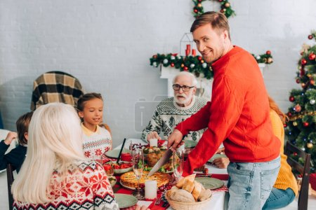Smiling man looking at camera while cutting pie on festive table near family