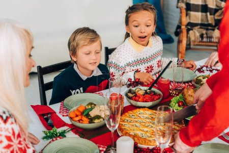 Selective focus of excited children looking at pie on festive table at home