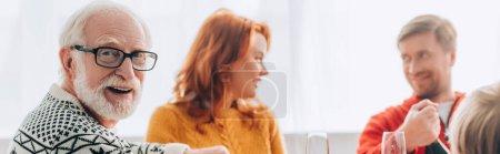 Photo pour Plan panoramique de grand-père souriant dans des lunettes près du couple parlant à la maison - image libre de droit