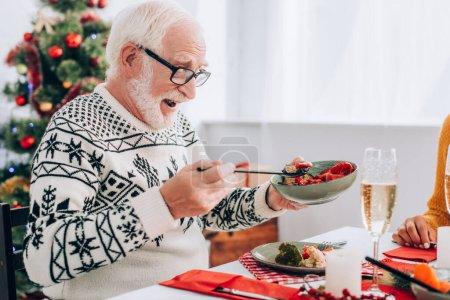 Photo pour Homme âgé dans des lunettes tenant bol avec des légumes, assis à la table festive - image libre de droit