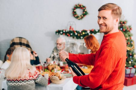 Photo for Selective focus of man opening champagne bottle near family sitting at table - Royalty Free Image