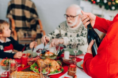 Photo for Selective focus of man opening champagne bottle near family and festive table - Royalty Free Image
