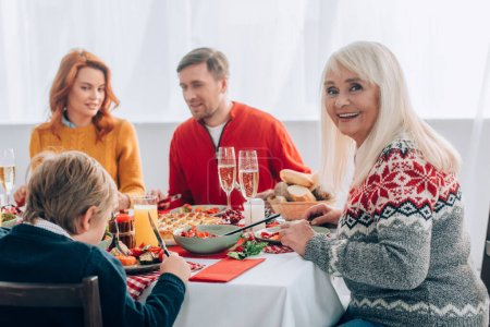 Selective focus of cheerful grandmother sitting near family at festive table