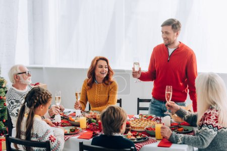 Hombre sonriente con copa de champán diciendo discurso cerca de la familia en la mesa festiva en casa
