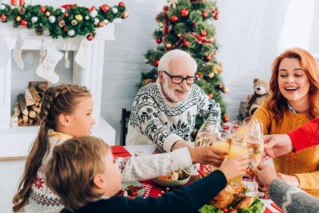 Photo pour Joyeux repas de famille, assis à une table festive près du feu et du pin de Noël - image libre de droit