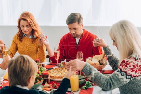 Photo for Selective focus of woman and man holding hands with family, sitting at table - Royalty Free Image