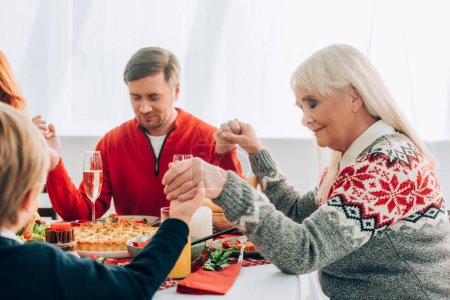 Selective focus of positive grandmother holding hands with family at home