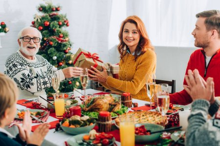 Woman and senior man holding gift box while sitting with family at festive table