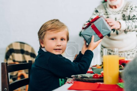 Photo for Selective focus of little boy holding gift box from grandfather, sitting at table - Royalty Free Image