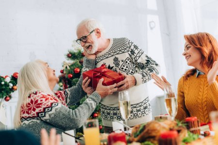 Smiling grandfather greeting wife with present near family applauding at home