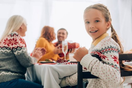 Photo pour Selective focus of smiling girl looking at camera, sitting at table with family - image libre de droit