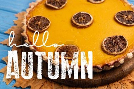 Photo pour Vue rapprochée de tarte à la citrouille décorée avec feuillage doré près de bonjour lettrage d'automne sur fond bleu - image libre de droit
