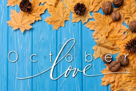 Photo for Top view of autumnal foliage with nuts and cones near october love lettering on blue wooden background - Royalty Free Image