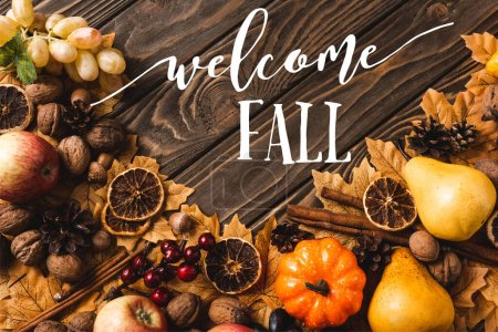 Photo for Top view of autumnal harvest and foliage near welcome fall lettering on brown wooden background - Royalty Free Image