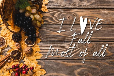 Photo pour Vue du dessus de la récolte automnale dispersée du panier sur le feuillage près de je l'amour automne surtout lettrage sur fond en bois - image libre de droit