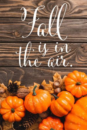 top view of autumnal decoration and pumpkins near fall is in the air lettering on wooden background