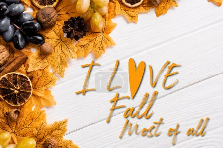 top view of autumnal decoration and grapes near i love fall most of all lettering on white wooden background