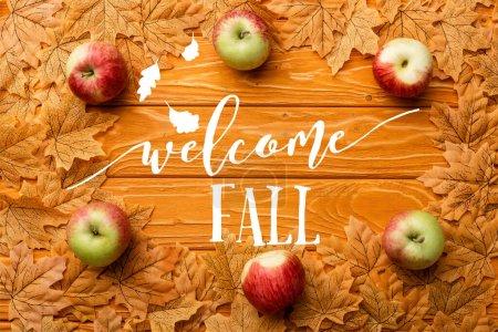 Photo pour Vue de dessus des pommes mûres et des feuilles près du lettrage d'automne bienvenu sur fond en bois - image libre de droit