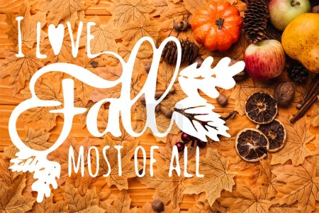 top view of autumnal decoration and food on golden leaves near i love fall most of all lettering on wooden background