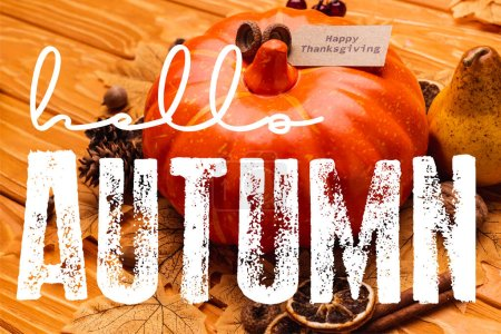 pumpkin with autumnal decoration and happy thanksgiving card near hello autumn lettering on wooden background