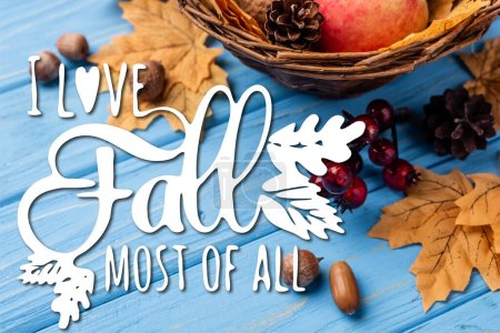 autumnal leaves, berries, acorns and cones near i love fall most of all lettering on blue wooden background