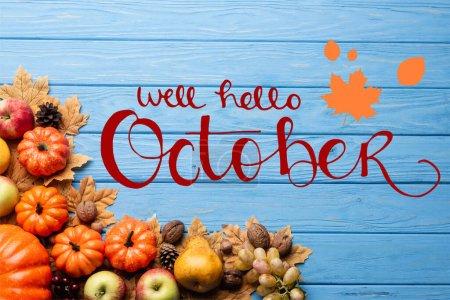 Ansicht der Herbsternte und Blätter in der Nähe von Brunnen Hallo Oktober Schriftzug auf blauem Holzgrund