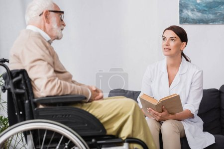 social worker in white coat reading book to aged disabled man in wheelchair on blurred foreground
