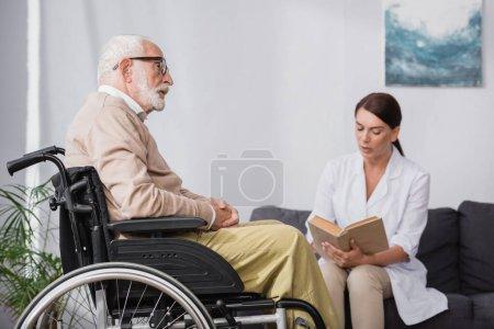 Photo pour Infirmière gériatrique livre de lecture à l'homme handicapé âgé sur fond flou - image libre de droit