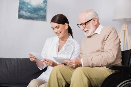 cheerful elderly man and social worker looking at photos at home
