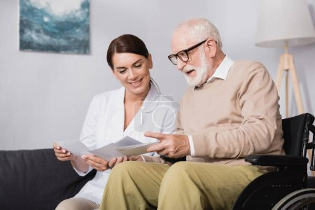 cheerful elderly man and smiling social worker looking at photos at home