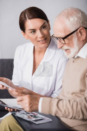 brunette social worker looking at aged mad while holding book on blurred foreground