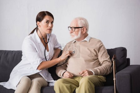 Photo for Social worker checking health of aged patient with stethoscope - Royalty Free Image