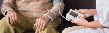 Altenpfleger untersucht alten Mann mit Tonometer zu Hause, Banner