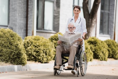 cheerful social worker walking with disabled elderly man reading newspaper in wheelchair