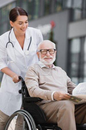 Lächelnder Sozialarbeiter, der mit einem fröhlichen alten Mann im Rollstuhl im Freien Zeitung hält