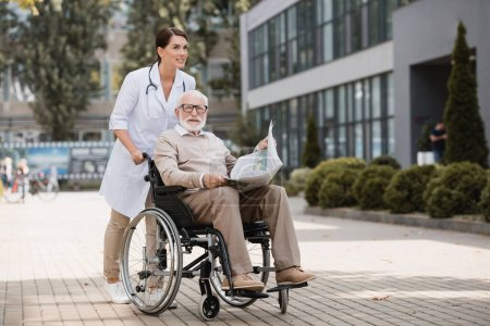 geriatric nurse walking with elderly disabled man in wheelchair with newspaper outdoors