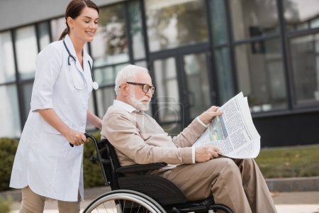 handicapped aged man reading book in wheelchair while walking with geriatric nurse outdoors