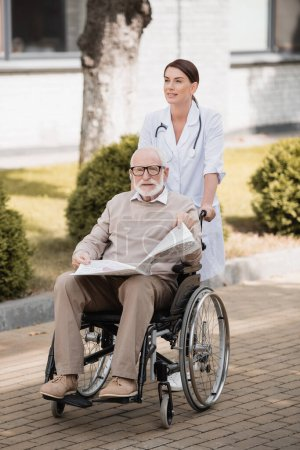 social worker walking with handicapped man holding newspaper in wheelchair