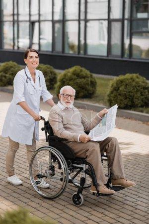 fröhliche Sozialarbeiterin blickt in die Kamera, während sie mit behindertem älteren Mann mit Zeitung im Freien spaziert