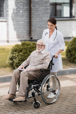 brunette social worker walking with aged handicapped man in wheelchair outdoors
