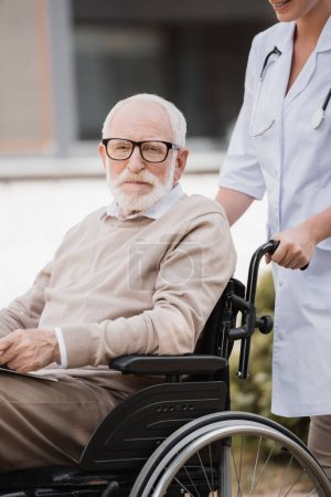 Photo for Elderly man in wheelchair looking at camera while waking with social worker outdoors - Royalty Free Image