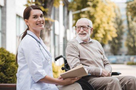 Photo pour Travailleur social joyeux regardant la caméra tout en étant assis près de l'homme handicapé âgé avec livre à l'extérieur - image libre de droit