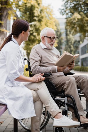 geriatric nurse sitting near aged disabled man reading book outdoors